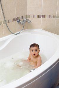 Ребенок купается в ванне.