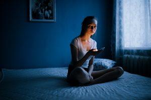 Работающая мама сидит на кровати и проверяет социальные сети