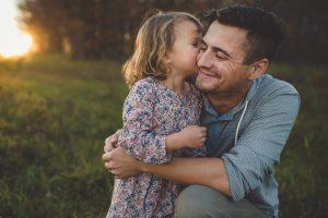 любимый ребенок целует папу в щеку