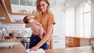 Лайфхаки для мам - мама протирает столы с ребенком на руках.