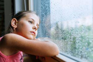 Грустная девочка смотрит в окно, потеря личности в резкльтате ошибки родителей в воспитании