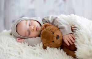 ребенок спит под одеялом с мишкой в руке