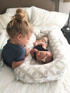 девочка играет со своей сестрой, когда вторая лежит в коконе-гнезде