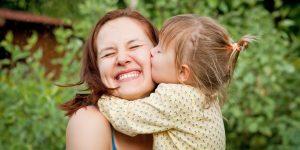 Маленькая девочка целует маму в щеку.