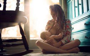 женщина сидит на полу и кормит ребенка грудью