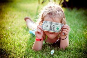 Родители решили дать карманные деньги детям, девочка с купюрой.