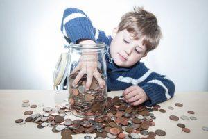 Мальчик лезет рукой в банку с карманными деньгами, монеты рассыпаны.