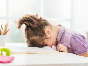 Девочке с головой на столе устала делать уроки.