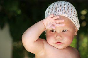 Малыш потеет в шапочке и закрывает глаза от солнца.