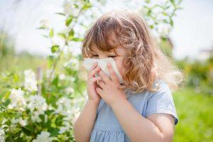 Девочка чихает в платок на фоне растений.