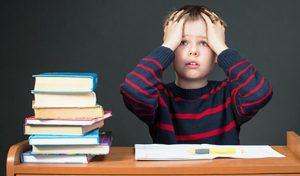 Ребенок делает уроки с озадаченным лицом.