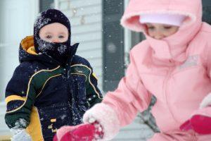 Дети играют на улице в зимней одежде.