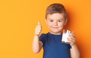 Мальчик сод таканом молока.Девочка пьет молоко. Давать ребенку молоко или нет?