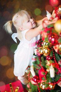 Девочка тянется, чтобы украсить елку.