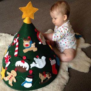 Ребенок наряжает детскую елку.Отличный способ защитить елку от ребенка и занять малыша.