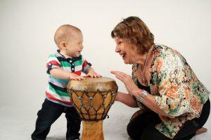 Ребенок играет на барабане с бабушкой.