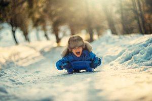 Ребенок не холодно, он радостный катится с горки.