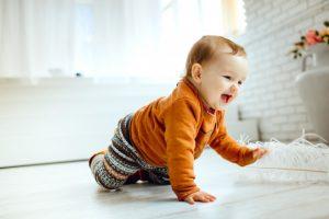 Ребенок ползет по белому полу - что нужно для здоровья детей.