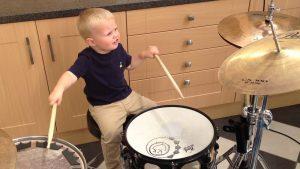 Ребенок в музыкальной школе на барабанах. преимущества музыкальной школы.