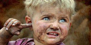 Чумазый ребенок, светловолосый мальчик с голубыми глазами - грязь на лице и руках.