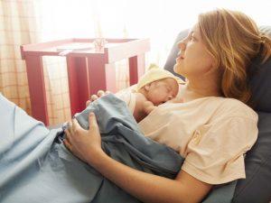 Женщина с ребенком лежит в родительной палате - беременность после кесарева.