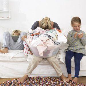 Уставшая мама с кучей белья для стирки. Светы родителям в карантин.