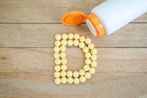 Витамин Д из коробки на деревянном столе.