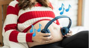 Беременная с наушниками у живота - ребенок в утробе слвшит музыку.